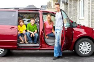 junge Familie, die im roten Geländewagen sitzt und lächelt foto