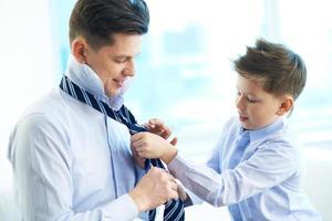 Kind hilft seinem Vater beim Anziehen einer Krawatte foto