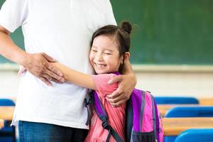 glückliches kleines Mädchen, das ihren Vater im Klassenzimmer umarmt