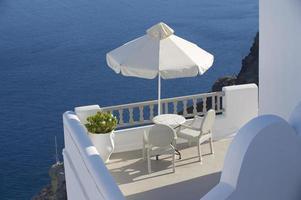 zwei Stühle unter Sonnenschirm mit Meerblick foto