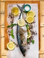 frische Makrele mit Zitrone und Kräutern über hölzernem Hintergrund foto