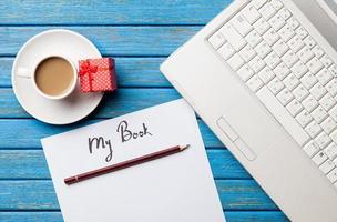 Kaffee und Papier mit meiner Buchinschrift in der Nähe von Notizbuch foto