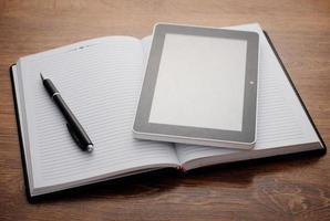 Tablet-Gerät auf offenem Notebook am Holztisch foto