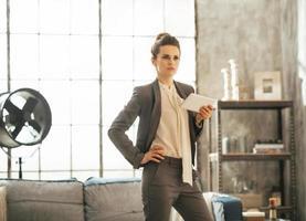 Geschäftsfrau mit Tablet-PC in Dachbodenwohnung foto