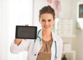 glückliche Ärztin Frau zeigt Tablet PC leeren Bildschirm foto