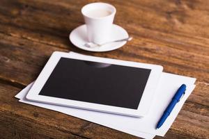 digitales Tablett und Kaffee auf altem hölzernem Hintergrund foto