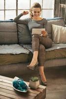 glückliche junge Frau mit Tablet-PC in Loft-Wohnung foto