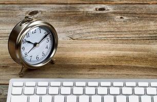 rustikaler hölzerner Desktop mit Retro-Uhr und Tastatur foto