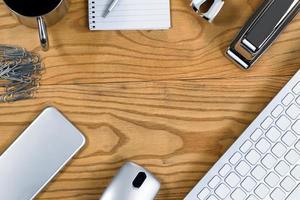 Holzschreibtisch mit Rand aus silberfarbenen Arbeitsgegenständen foto