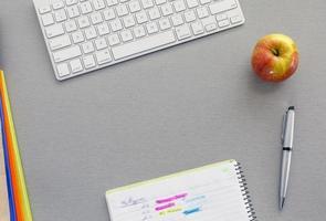 Büroarbeitsplatz auf grauem Schreibtisch mit rotem Apfel foto