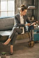glückliche Geschäftsfrau mit Tablet-PC in Loft-Wohnung foto