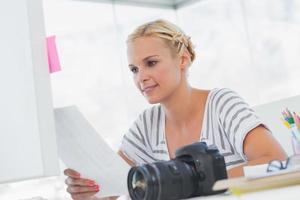 hübscher Bildbearbeiter, der ein Kontaktblatt betrachtet