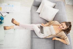 lächelnde junge Frau, die auf Sofa mit Tablette PC sitzt foto