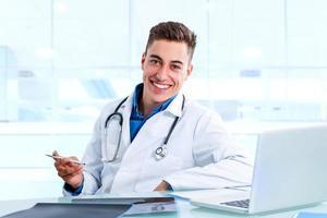 medizinischer männlicher Arzt am Schreibtisch mit Laptop und Röntgenstrahlen. foto