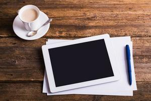 digitales Tablett und Kaffee auf altem hölzernem Hintergrund