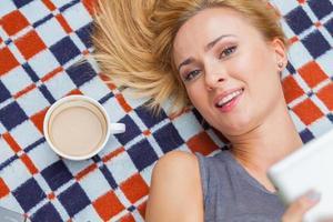 sinnliche blonde Frau, die im Park auf Decke liegt. foto