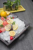 frischer forelle mit Zitrone auf einem holztablett foto