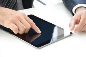 Geschäftsmannhand, die Tablet-PC-Bildschirm auf dem Tisch berührt foto