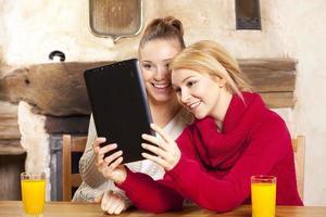 Zwei schöne Frauen arbeiten an der Tablette foto