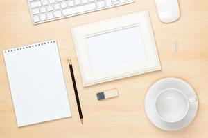 Fotorahmen auf Bürotisch mit Notizblock, Computer und Tasse foto