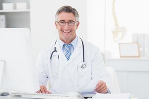 glücklicher männlicher Arzt, der Dokumente am Tisch überprüft