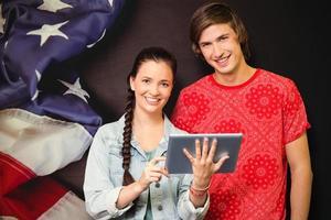 zusammengesetztes Bild von lächelnden Klassenkameraden mit Tablette PC foto