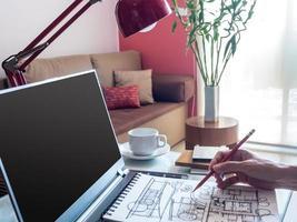 Designer arbeitet mit Laptop und Architekturzeichnung im modernen Arbeitsbereich foto