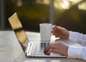 Geschäftsmann, der mit Laptop und Tasse Kaffee bei Sonnenuntergang arbeitet foto