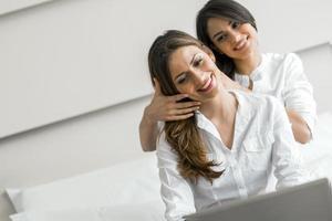 zwei schöne Frauen, die im Bett ein Notizbuch benutzen