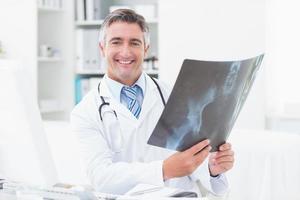 glücklicher Arzt, der Röntgen in Klinik hält