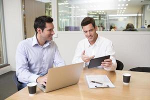 zwei ungezwungene Geschäftsleute, die in einem modernen Büro mit la zusammenarbeiten foto