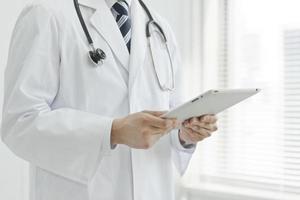 der Arzt, der einen Tablet-PC betreibt foto