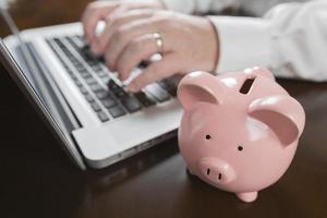 Sparschwein in der Nähe von männlichen Händen, die auf Laptop tippen foto