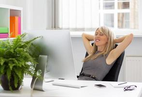 entspannte Frau genießt erfolgreichen Tag bei der Arbeit foto