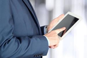 junger Geschäftsmann, der an einem digitalen Tablett arbeitet