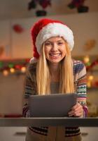 Porträt des Teenager-Mädchens in der Weihnachtsmütze unter Verwendung des Tablet-PCs foto