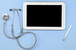 Tablette mit leerem Bildschirm und Stethoskop foto