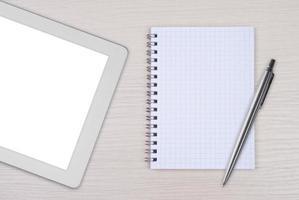 Tablet-PC mit Notizblock und Stift auf Holzschreibtisch foto