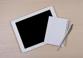 Tablet-Computer mit Notizblock und Stift auf Holzschreibtisch foto