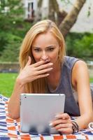 sinnliche blonde Frau, die im Park auf Decke mit Tablette liegt.