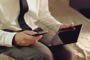 einsamer Geschäftsmann im Hotelzimmer, der auf dem Bett sitzt foto