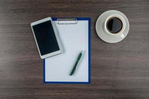 Tablette, Papier und Stift mit einer Tasse Kaffee