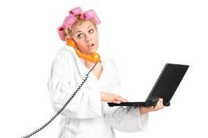 überraschtes Mädchen, das Laptop hält und am Telefon spricht foto