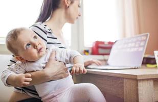 junge Mutter arbeitet von zu Hause aus foto