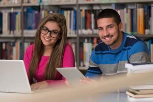 glückliche Studenten, die mit Laptop in der Bibliothek arbeiten foto