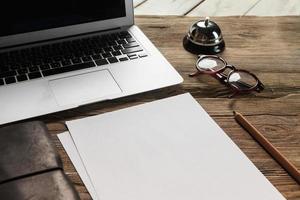 der Laptop, leeres Papier, Brille und kleine Glocke auf dem foto
