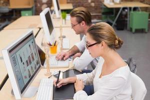 konzentrierte Gelegenheits-Bildbearbeiter mit Digitalisierer im Büro foto