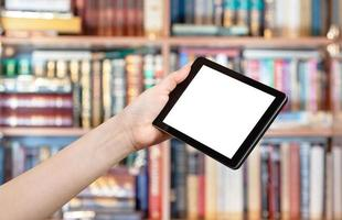 Hand hält Tablet-PC in der Bibliothek foto