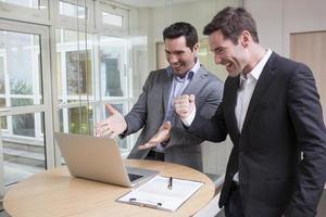 erfolgreiche lächelnde Geschäftsleute im Büro, mit erhobenen Armen foto
