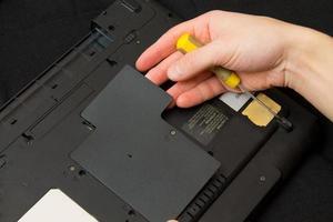 Mann öffnet einen Laptop mit Schraubenzieher foto